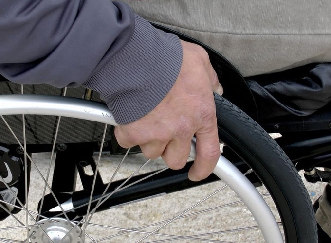 Closeup picture of a wheelchair users hand on wheel