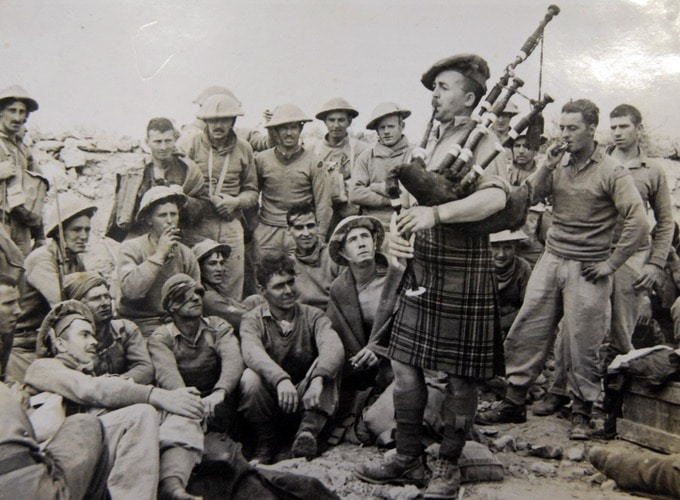 The Black Watch Regiment Tobruk 1942. Piper Rob Roy plats the pipes as injured soldiers look on
