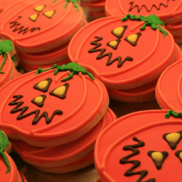 Pumpkin shaped cookies with orange icing and smiling faces