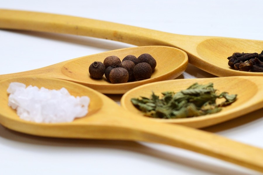 four wooden spoons each with different herbs and spices