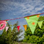 colourful bunting blowing in the wind with green trees in the background