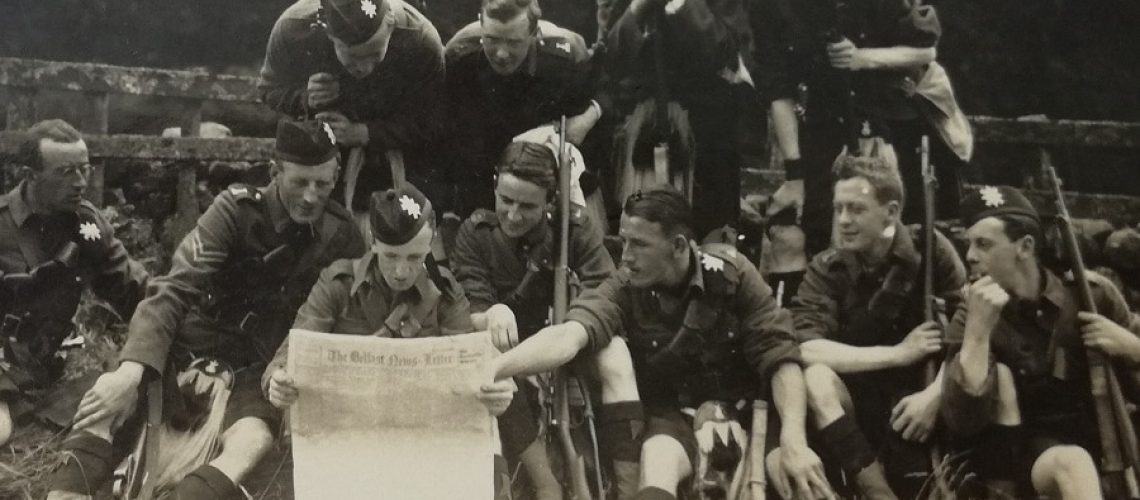 black and white photograph of Black Watch soldiers sitting on the grass reading a newspaper